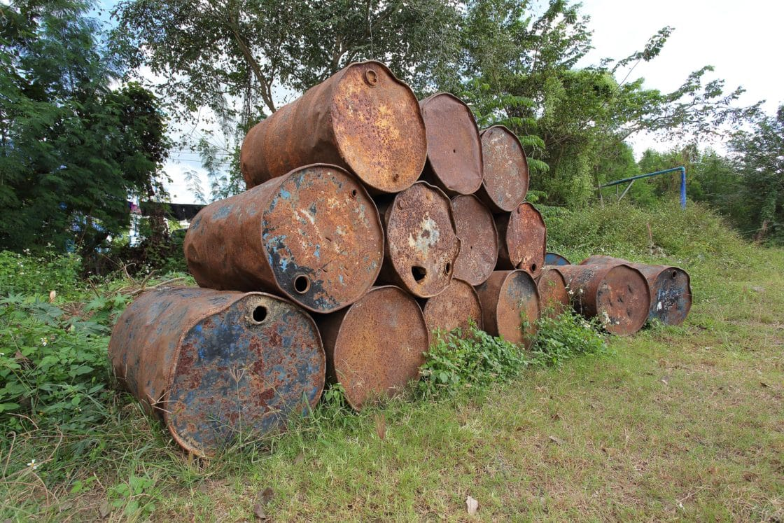 old rusty metal fuel tanks stacked in a row