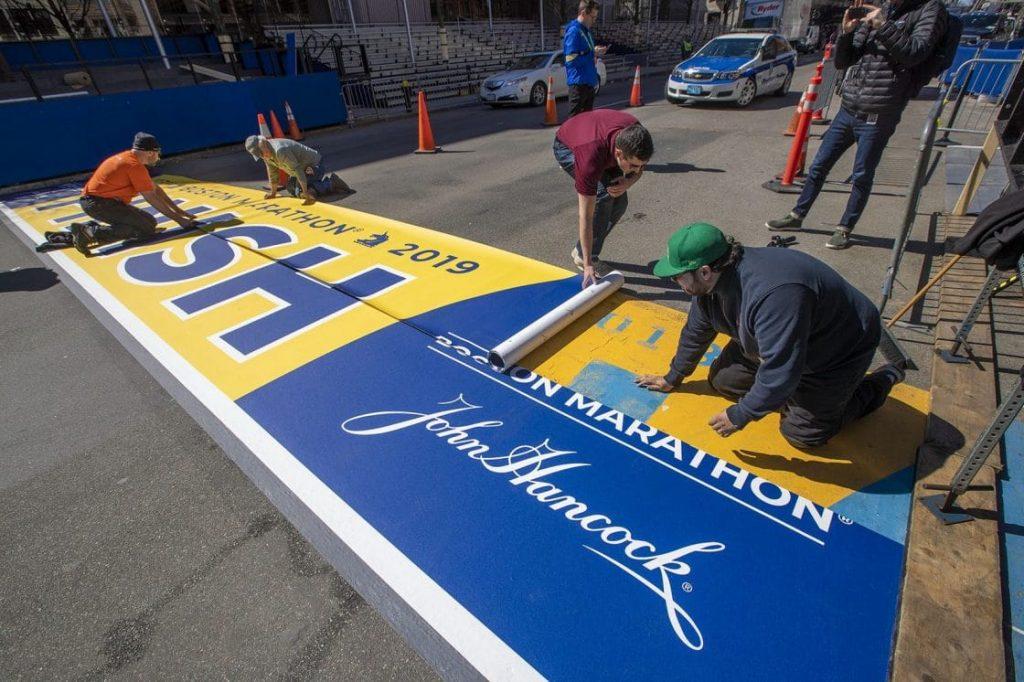workers paint boston marathon finish line on boylston street in boston