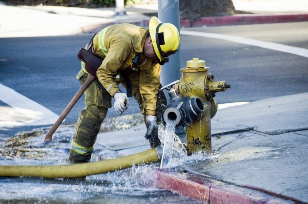 firefighter attaching hose to hydrant