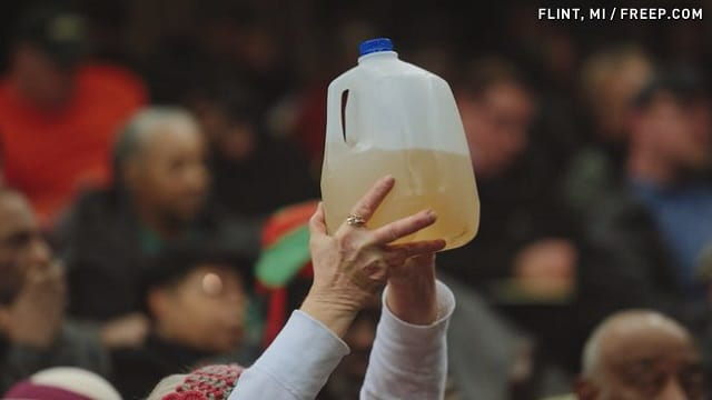lead contaminated water being displayed in a milk jug to show contamination levels.