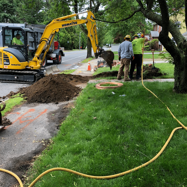 Lead service replacement program in Newton, MA. Excavator and men.