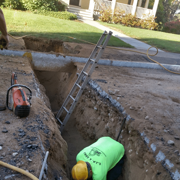Lead service replacement program in Newton, MA. Excavator and men. Construction worker replacing pipes.